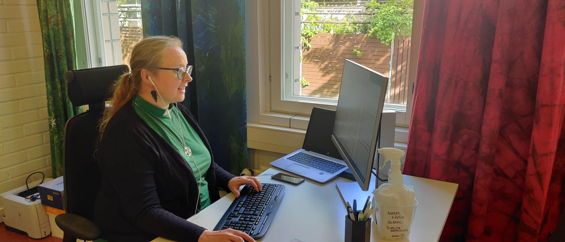 Nainen vihreässä virkapaidassa ja mustassa neuletakissa istuu tietokoneen ääressä ja kuulokkeet korvilla