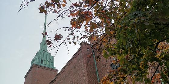 Mikael Agricolan kirkon kirkontorni, jonka vieressä näkyy syksyisiä puun oksia ja lehtiä.